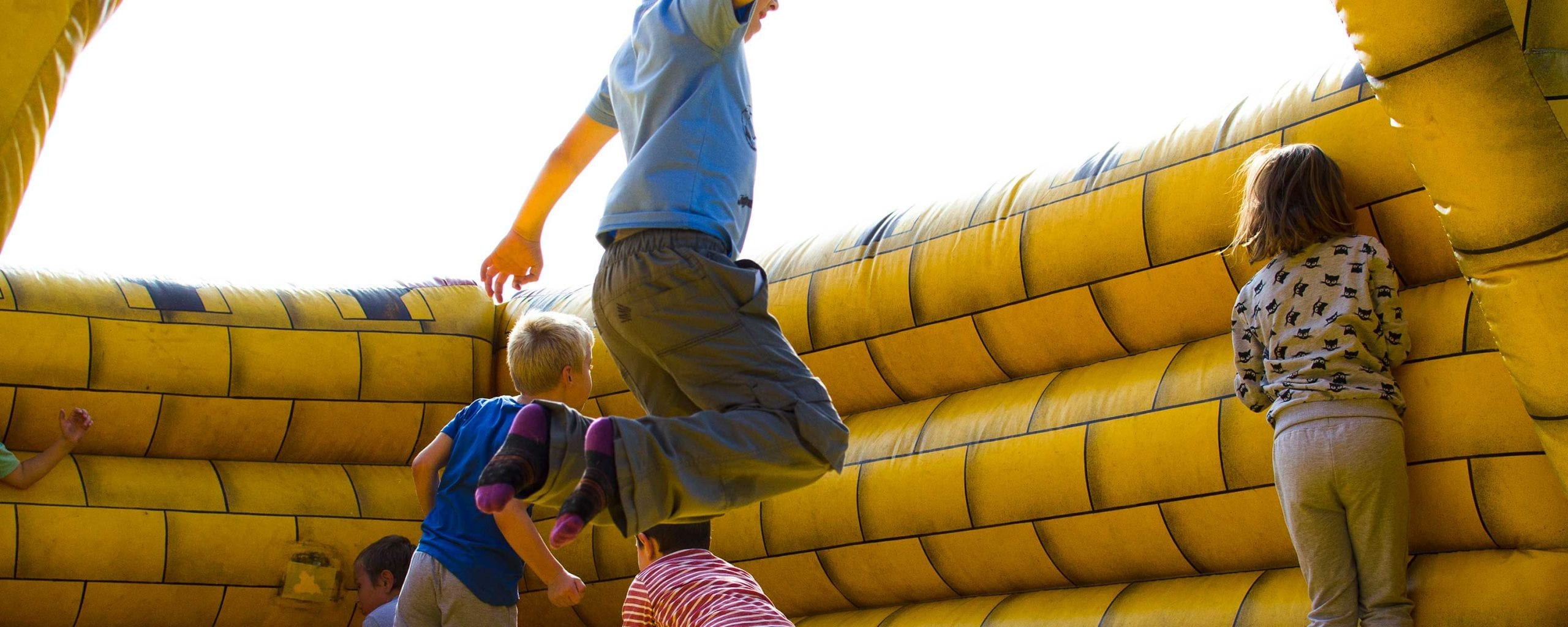 kids having fun at an event on an inflatable moon bounce bounce house