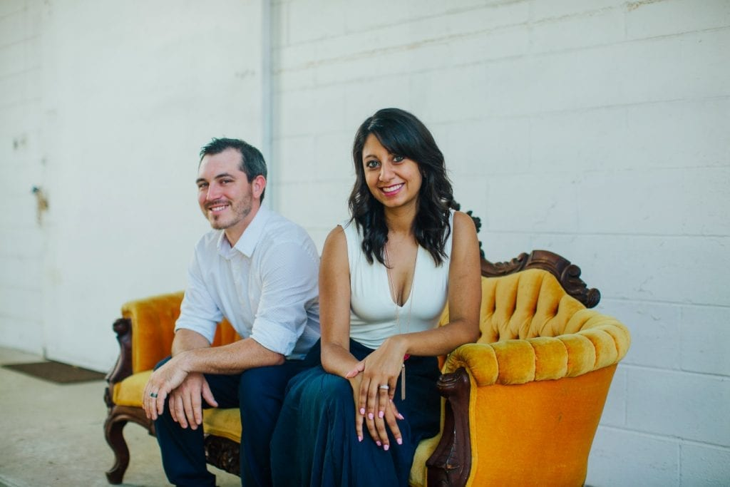 Rachel and Jordan Strickland of Savannah Vintage & Event Rentals. The couple is sitting on a couch.