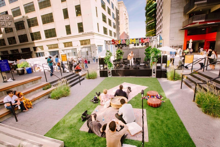 The Top Event Profs Know How Their Clients Really Feel. ROW DTLA Spring Market. People sitting on the grass and watching a musician perform on stage.