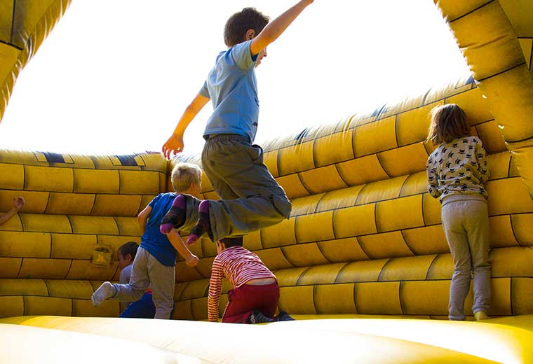 kids having fun playing on an inflatable moon bounce bounce house