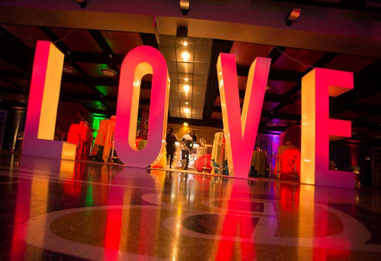 "fun activation that says ""LOVE"" in red light at an event"