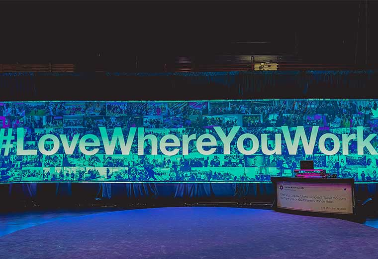 """love where you work"" written on draping with lighting on a stage at an event"