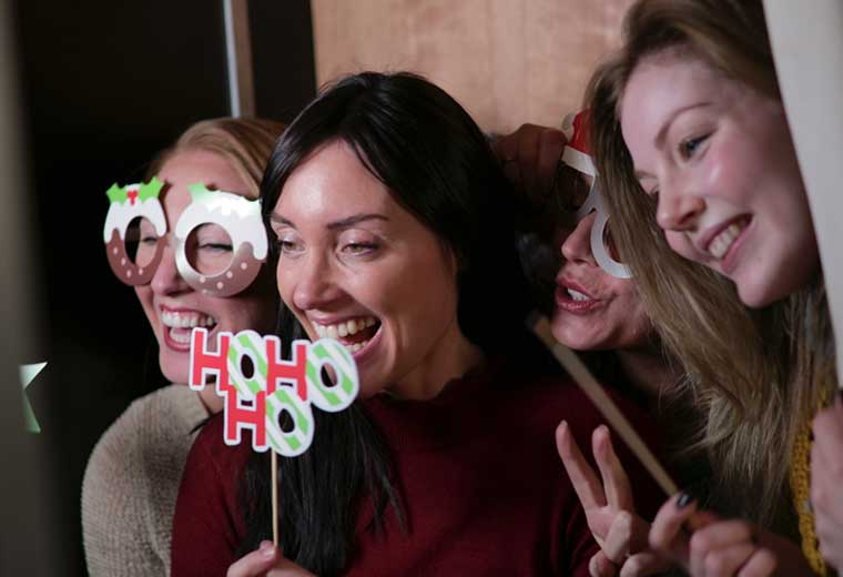 women using a photo booth at an event