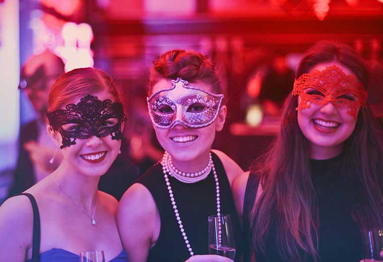 Women in masks at a masquerade event venue