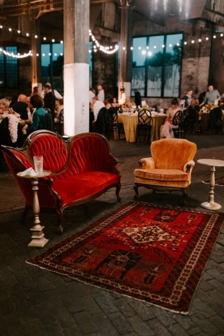Wedding lounge setup with vintage furniture and carpet with fairy lights